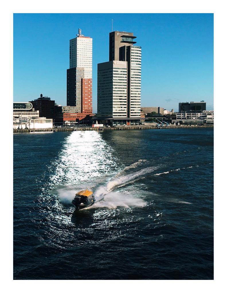 Foto van een watertaxi op de Maas, met op de achtergrond de wolkenkrabbers van de Kop van Zuid in Rotterdam