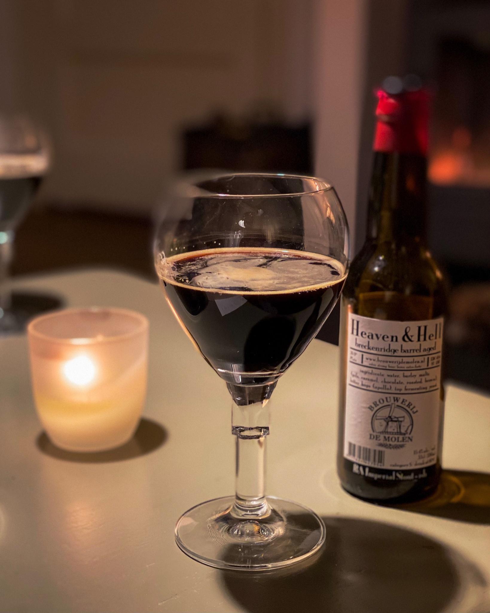 Donker bier in een glas, met ernaast een fles Heaven & Hell van brouwerij de Molen
