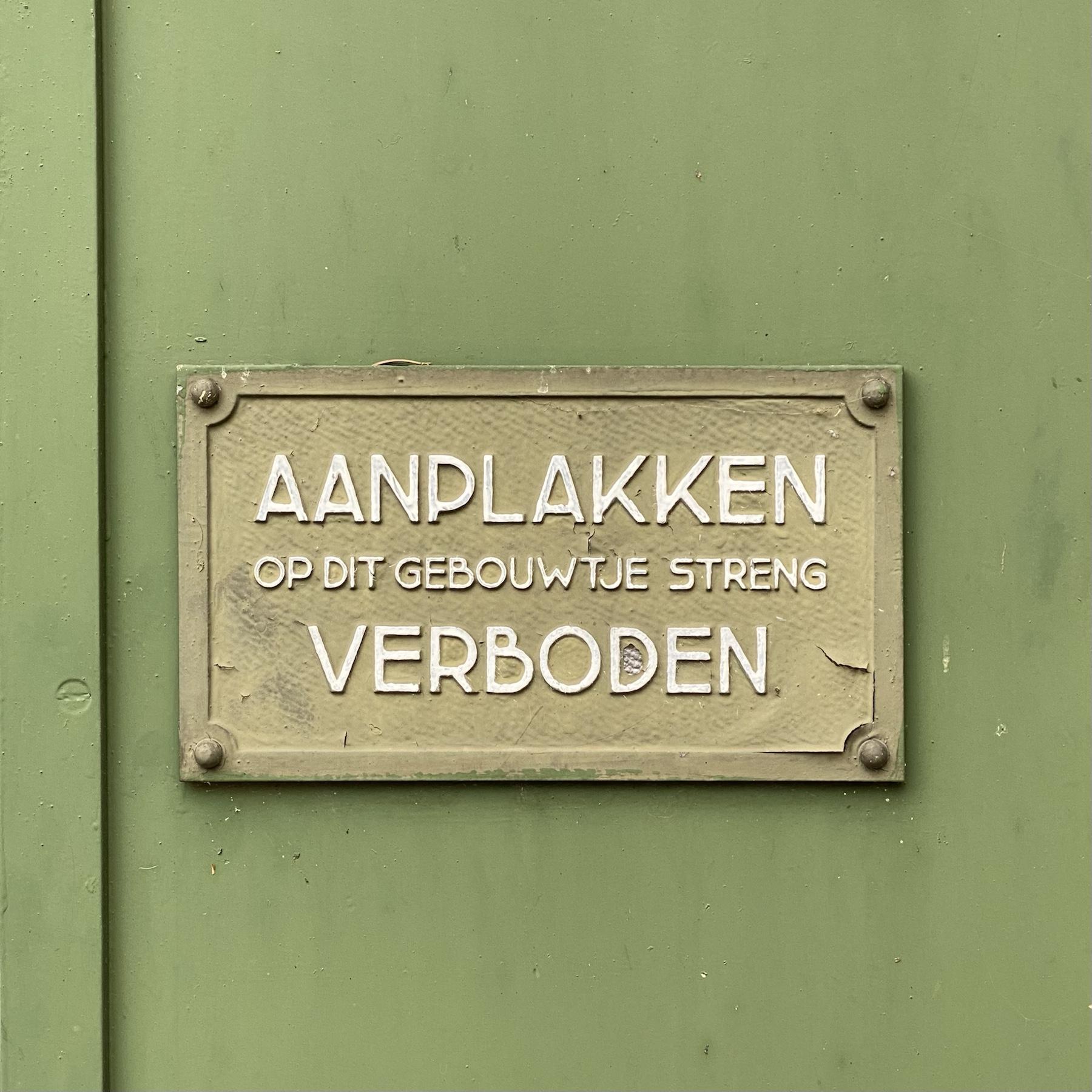 Bord met de tekst 'Aanplakken op dit gebouwtje streng verboden'
